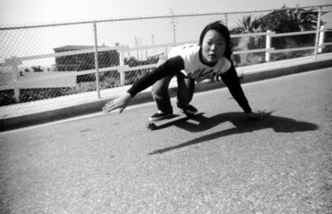 [peggy oki demonstrating a burt move, dragging her hand on asphalt as if she were surfing]